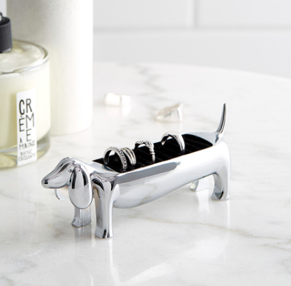 A dog-shaped ring holder on a marble vanity
