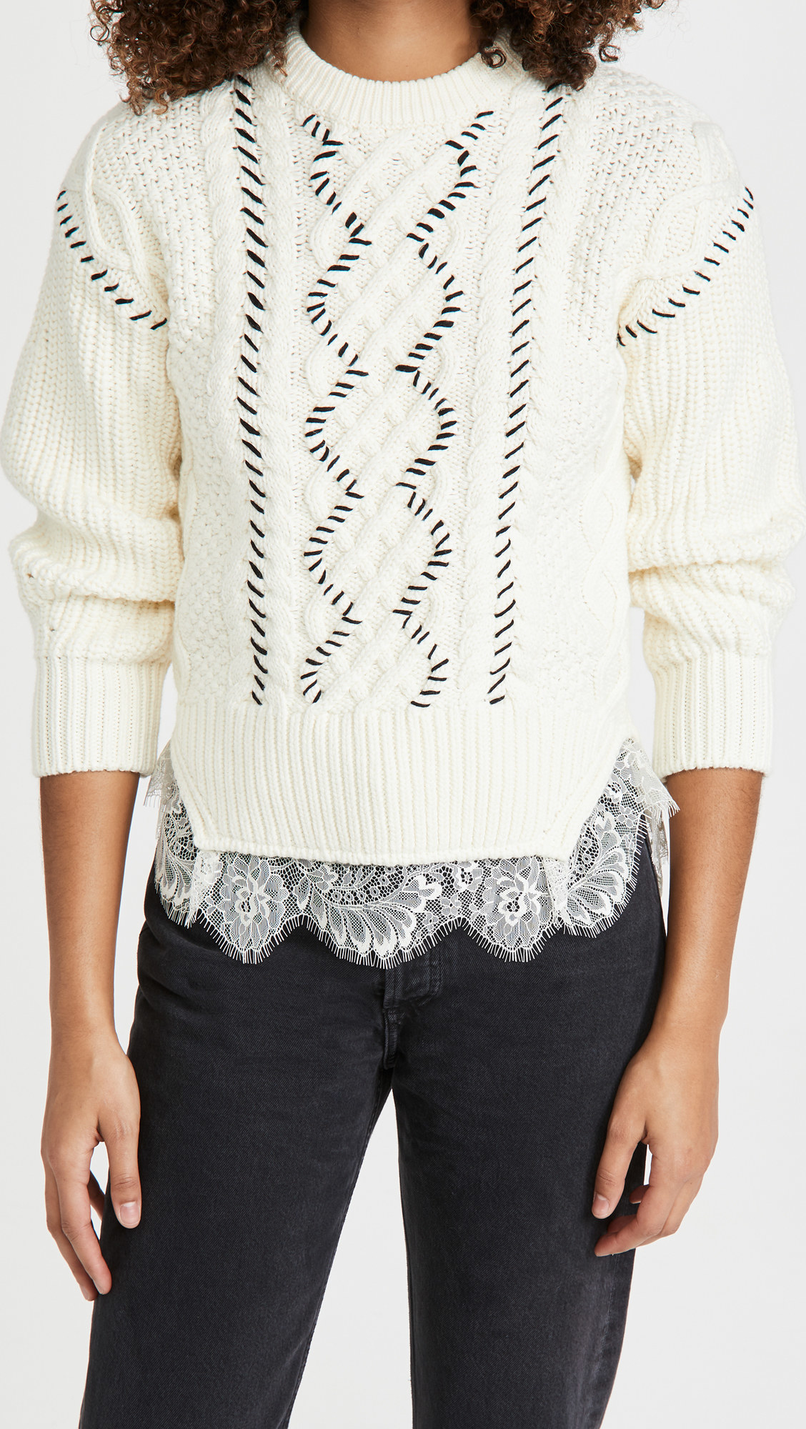 A model wearing the white cable knit sweater with black stitch details and white lace at the bottom with black jeans