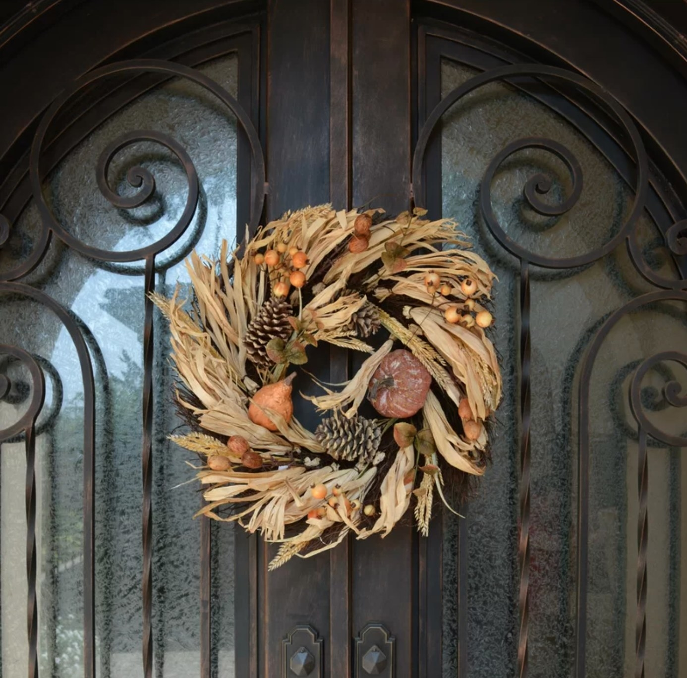 The seasonal wreath with pinecones and pumpkins on a double door
