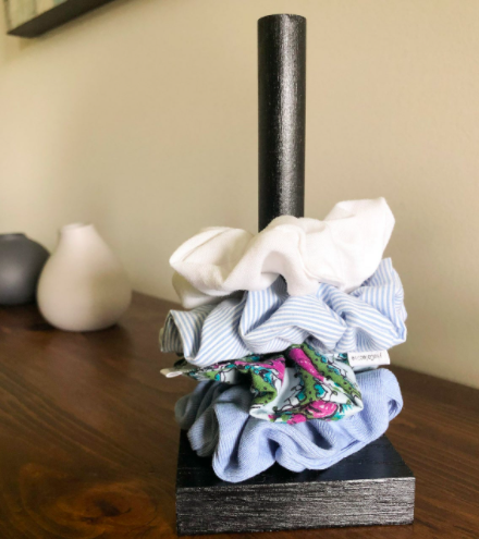 A close up of the wooden scrunchie holder holding three scrunchies