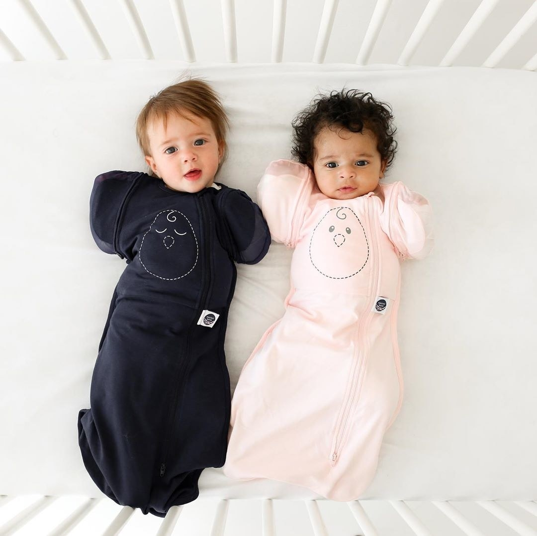 Two babies lying in a crib in sleep sacks