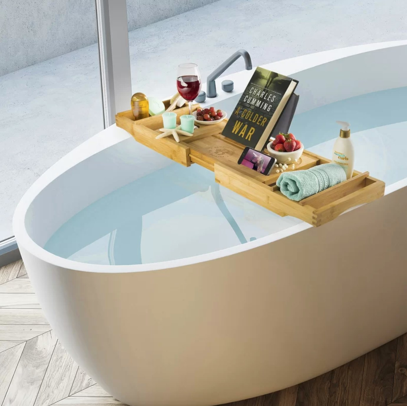 The bathtub tray in bamboo holding wine, fruit, and towels