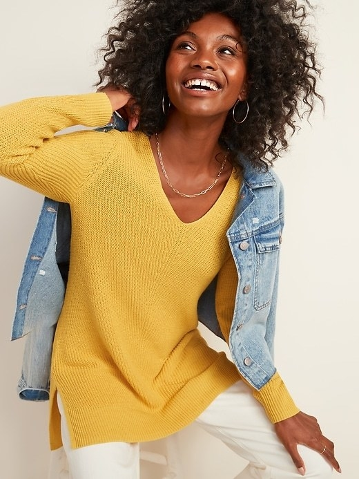 Model wearing the sweater in yellow under a blue jean jacket