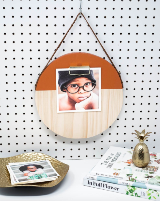 Circular orange and wood board with an instant-print photo on a white wall above a desk filled with a decorative tray and floral books
