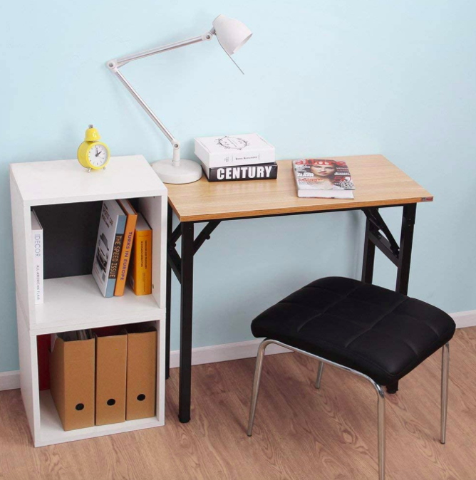 Folding desk with wooden top and black legs next to a black stool and small white bookcase