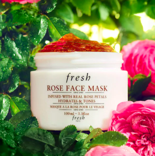 A face mask on a lush green background with roses