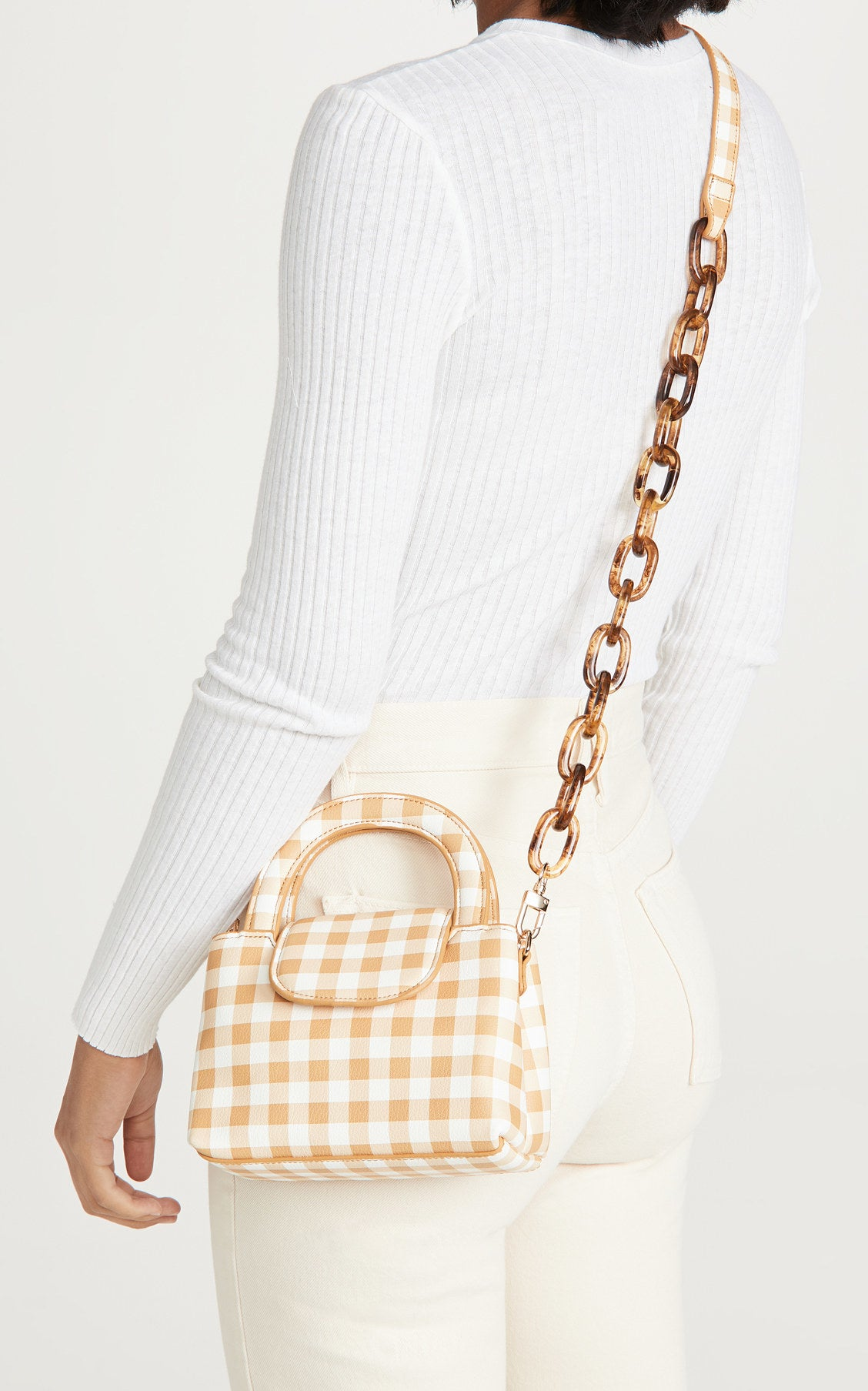 A model carrying the white and yellow top-handle bag with a tortoiseshell effect chain strap as a crossbody with white jeans