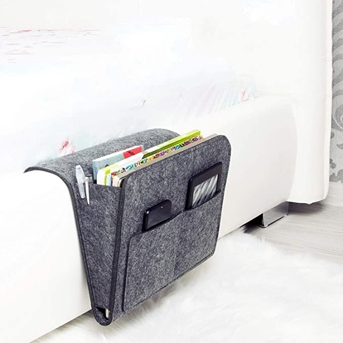 Grey bedside caddy on a white bed.