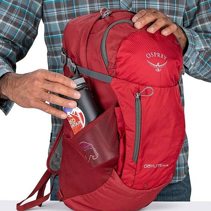 a person's hand putting a drink in the side-pocket of the bag