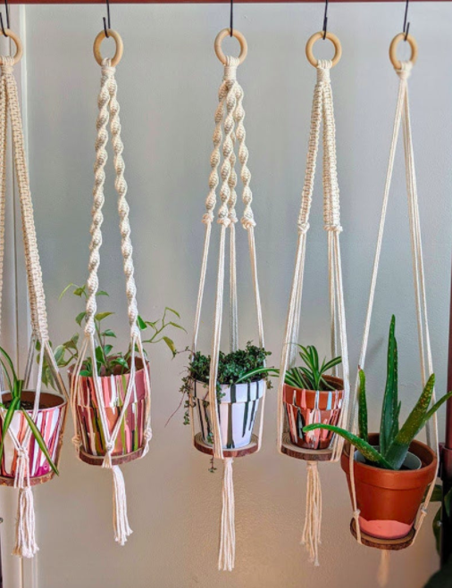 White macrame plant hangers holding colorful paint-drip planters with various green plants