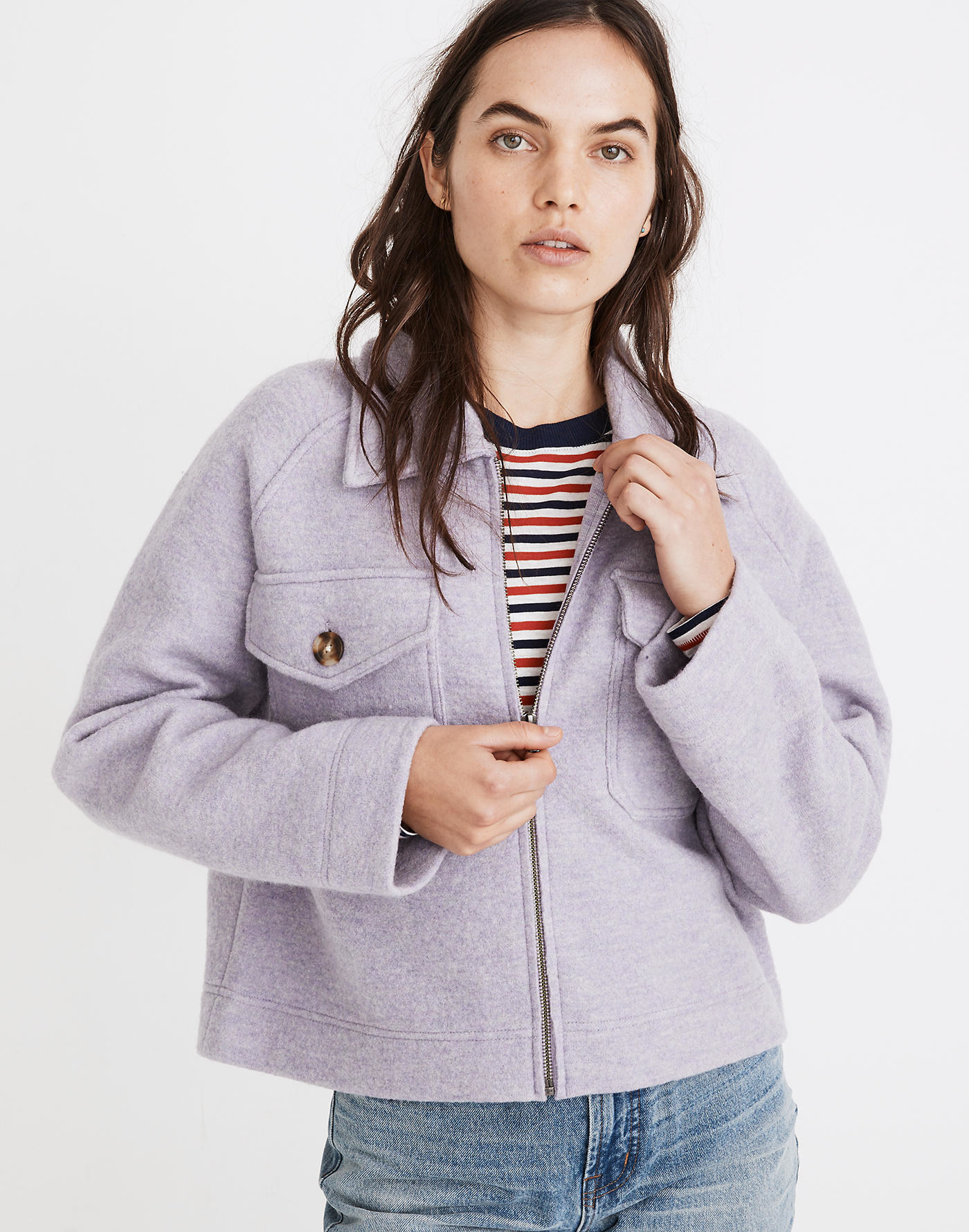 A model wearing the boxy lavender zip-up jacket with faded jeans