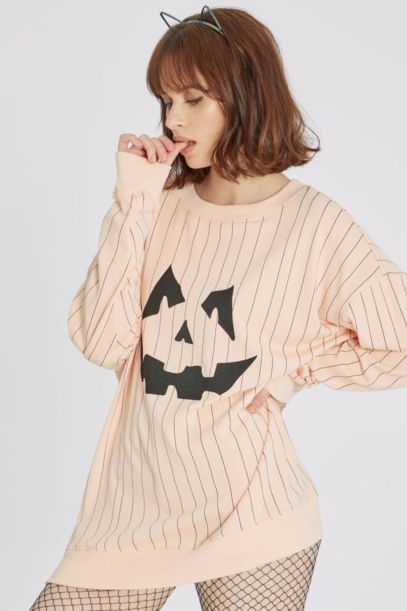 model wearing a light orange sweatshirt with stripes and a jack-o'-lantern design on the front
