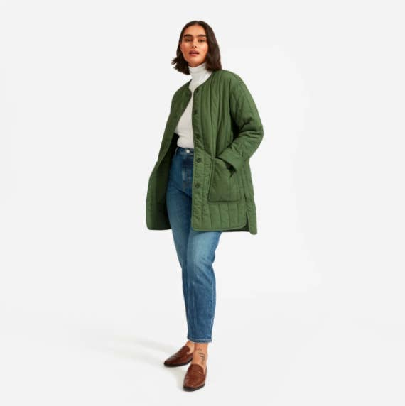 model wearing olive green quilted button down coat with front pockets
