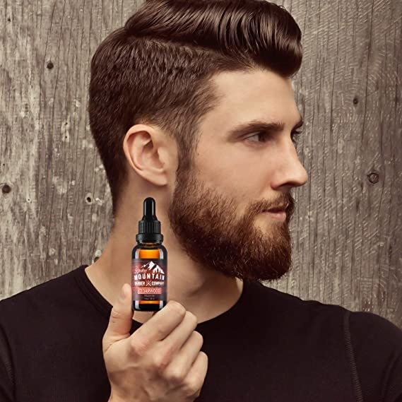 A person golds a beard oil and shows their beard