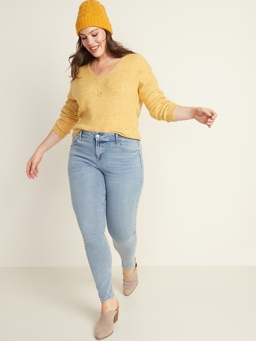 Model wearing the jeans with a yellow top tucked in, boots, and a beanie