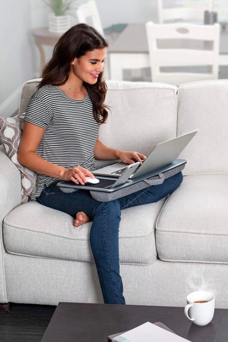 Model uses gray lap desk to work on laptop while sitting on a gray couch