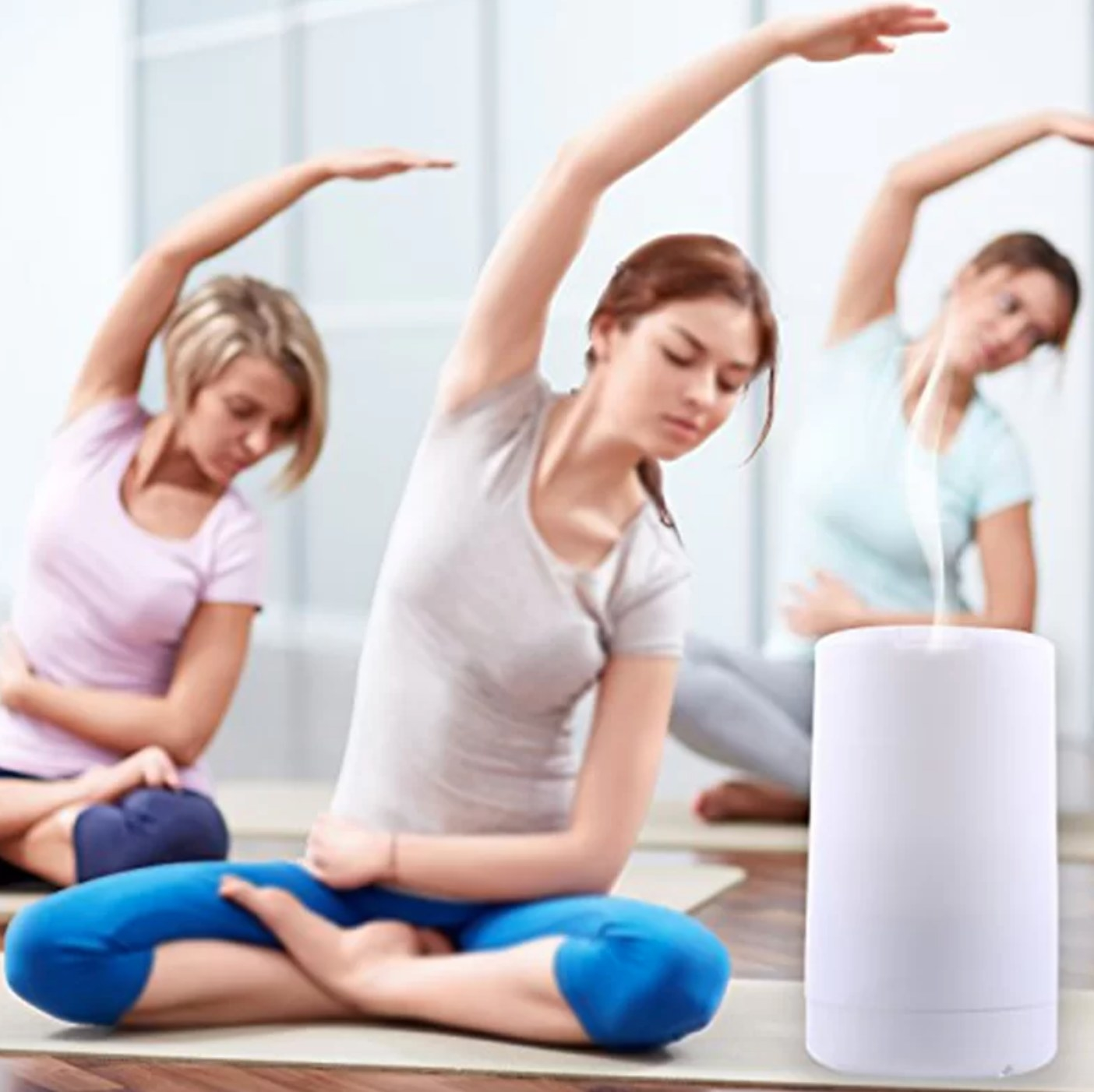 The diffuser in white being used in a yoga class