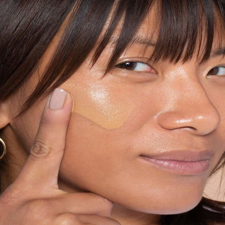 model with a swatch of product on her cheek