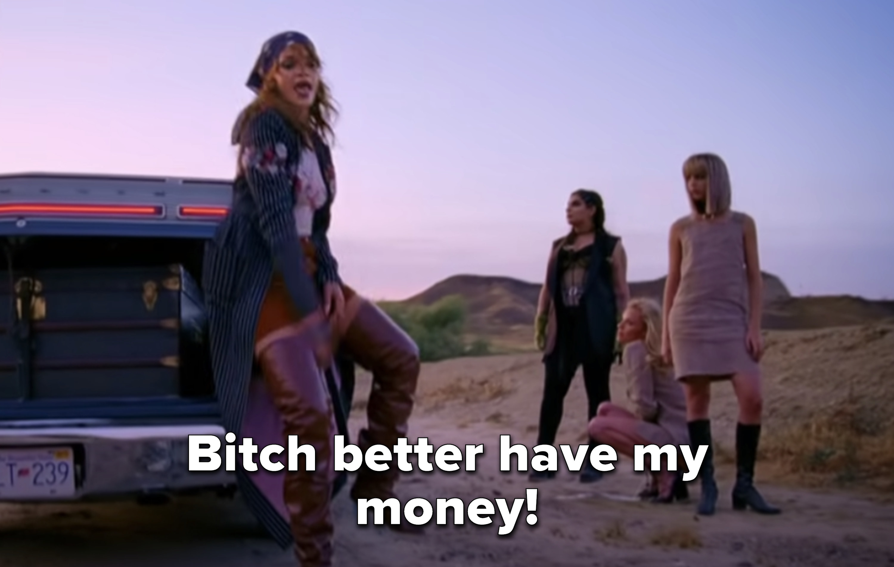 """Rihanna in front of an open trunk in the desert saying """"Bitch better have my money!"""""""
