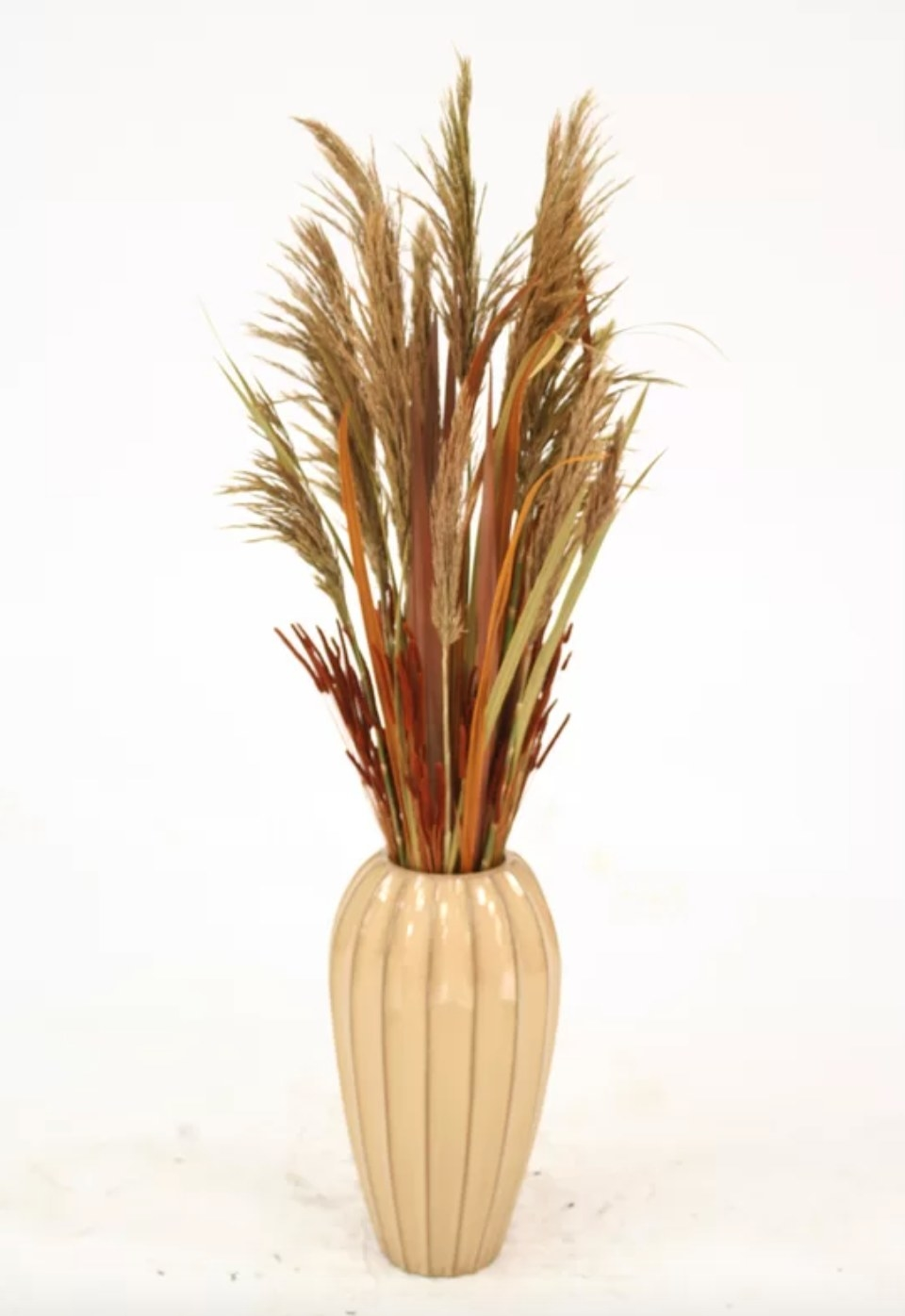 The dried grass plant in beautiful fall colors in a beige vase