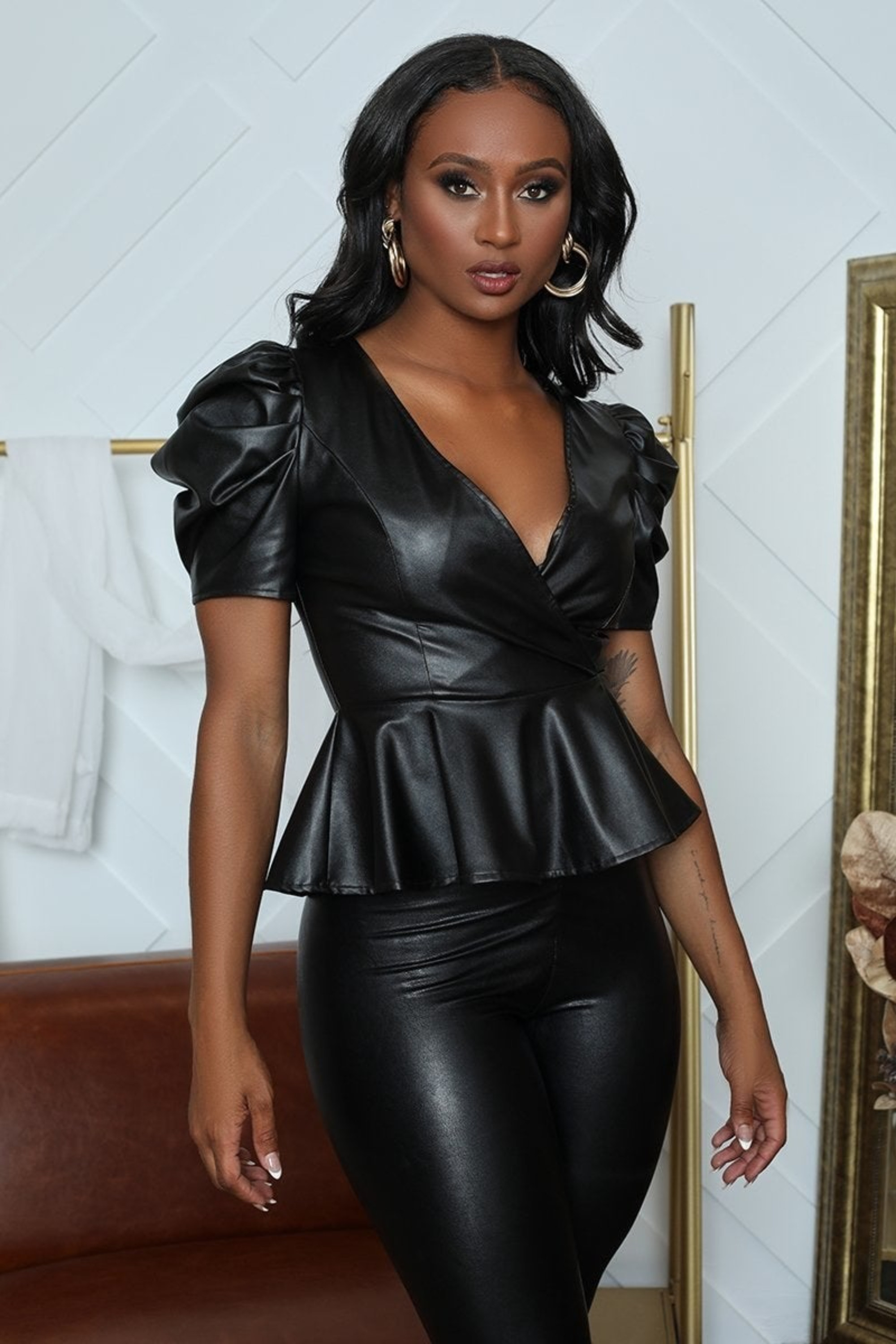 A model wearing the black short puffed sleeve, V-neck top