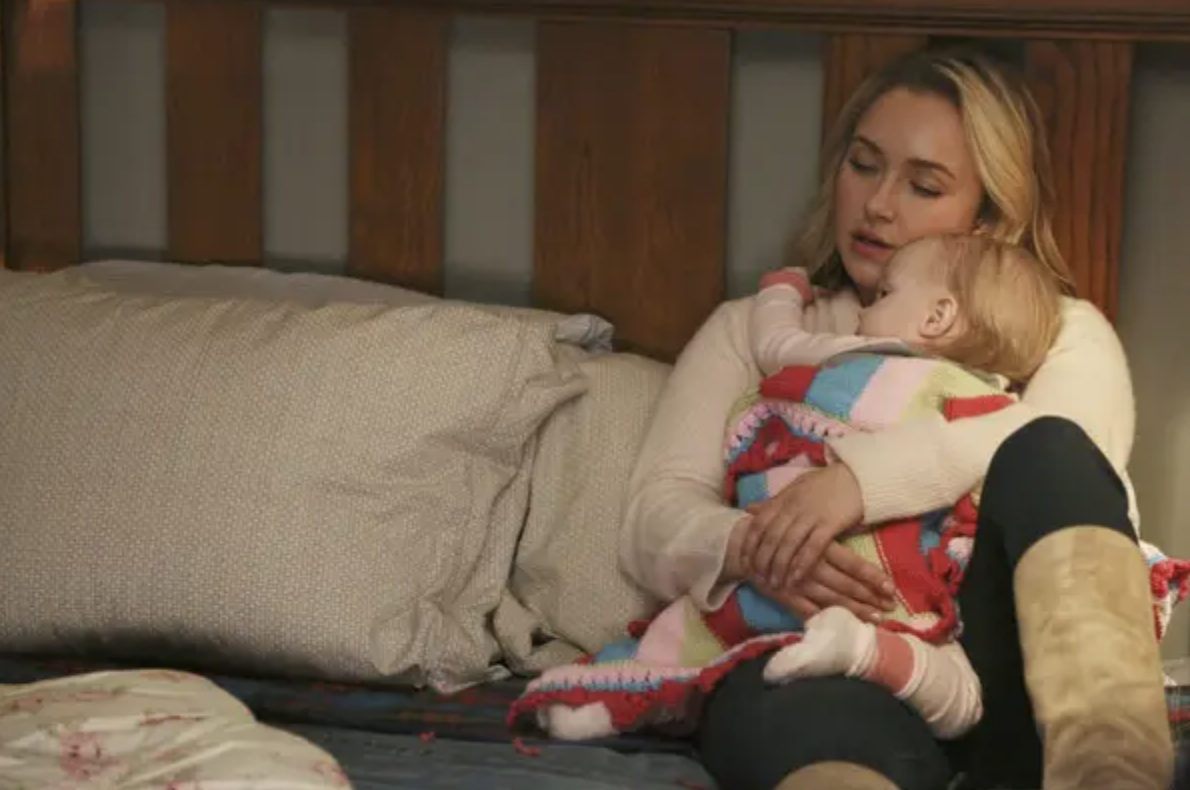An exhausted mom holds a baby in bed