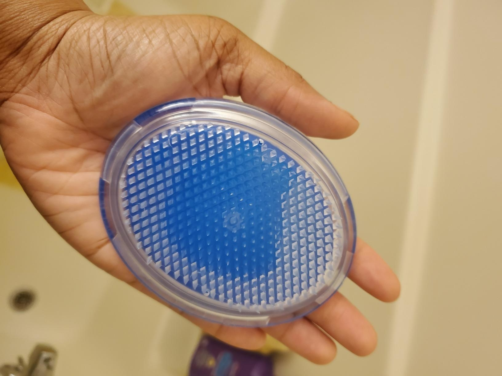 A reviewer holding the ergonomic brush with hard-ish silicone bristles