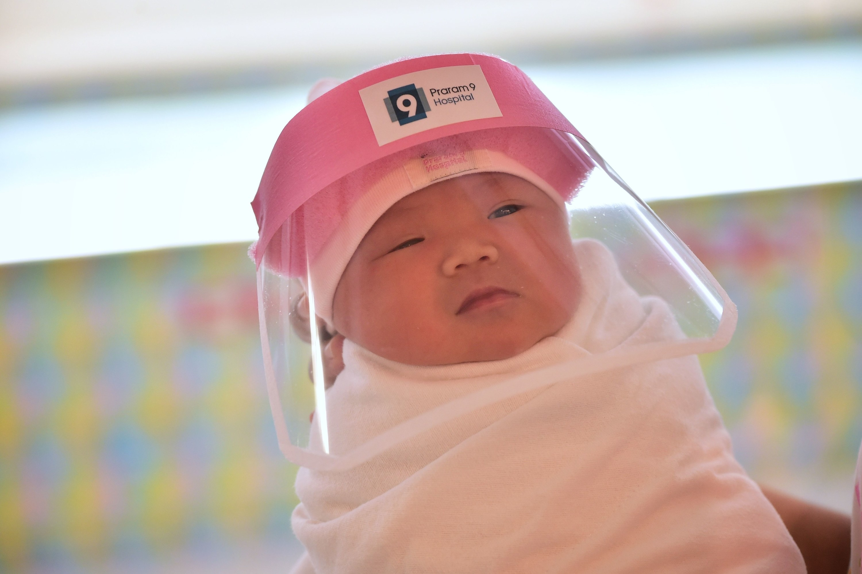 A newborn wears a facial shield