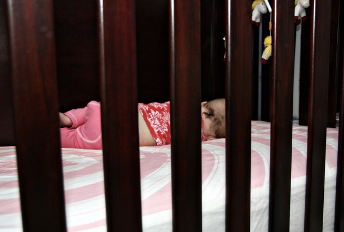A baby sleeps in a crib
