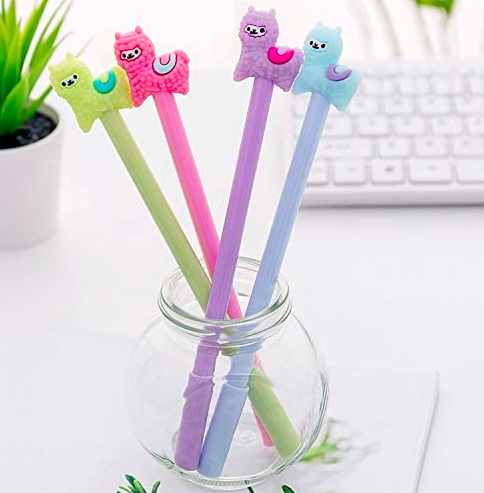 Green, pink, blue, and purple pens with little fluffy llamas on top in a small clear pen holder