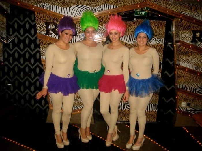 Four friends dressed in unitards with colored tutus that match their color wigs