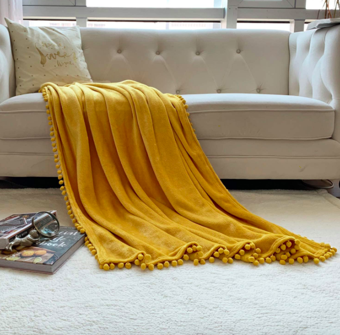 Mustard yellow blanket with pom-pom fringe on top of a white couch