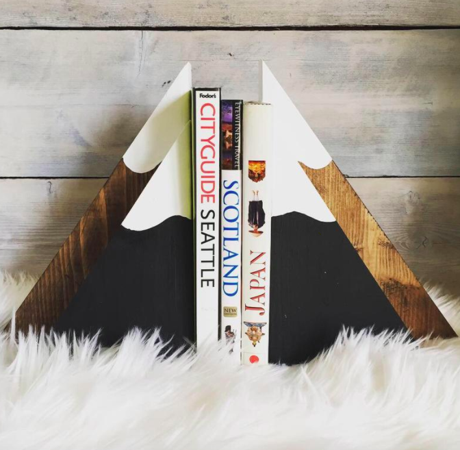 Mountain-shaped wood and white mountain bookends holding three books together on a shaggy white blanket