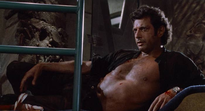 Jeff Goldblum in Jurassic Park looking concerned while laying back with his chest exposed and a bandage on his leg
