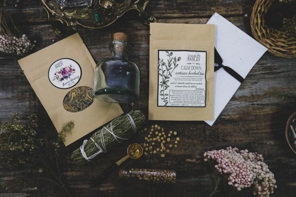 loose leaf teas, a glass bottle with a cork, dried herbs and spices, and other items