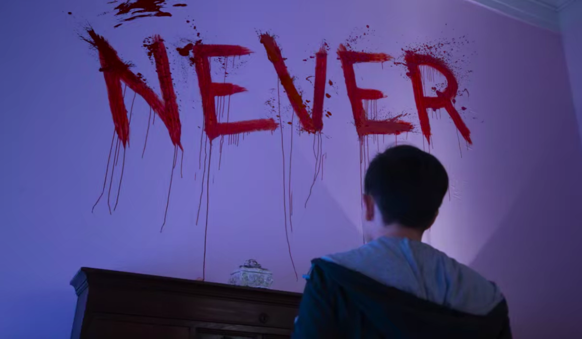 """Creepy """"Never"""" spelled out in blood red paint on the walls"""