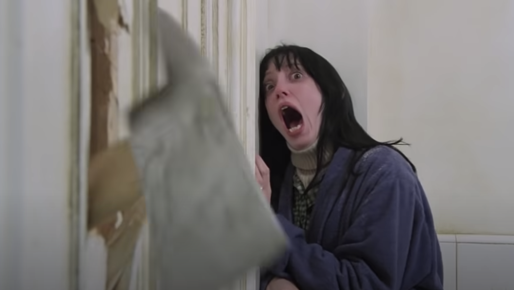 Shelley screaming as Jack uses an axe to break down the door of the bathroom she is in in The Shining