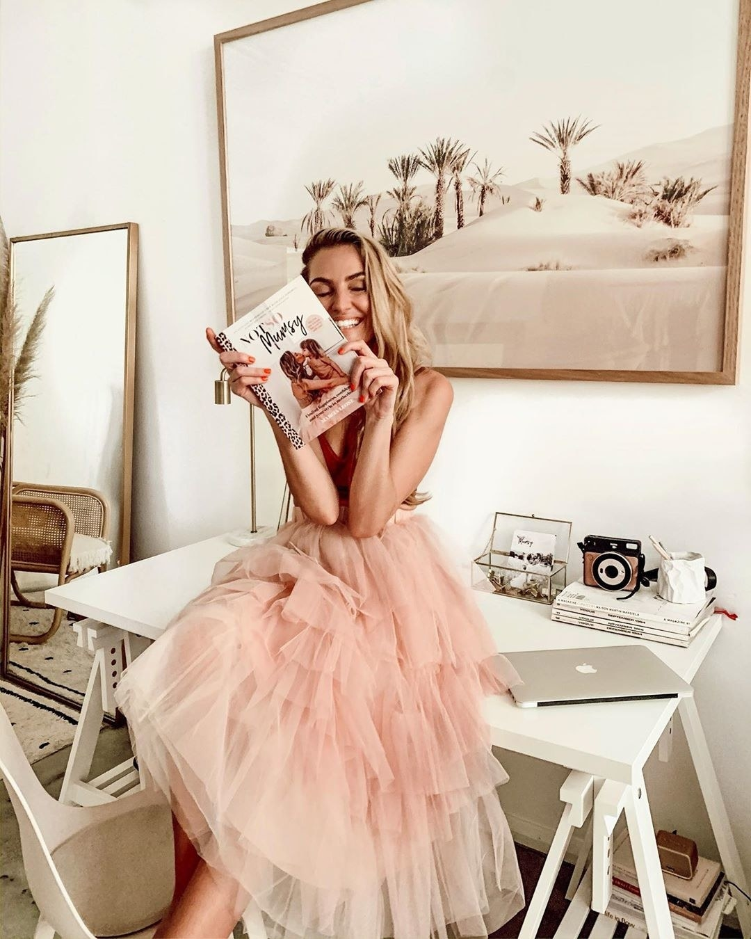 Woman in a pink tulle dress sitting on a desk and holding her book up