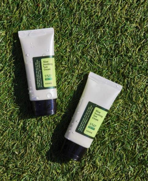 The Corsx Sun Cream bottles sitting on top of grass