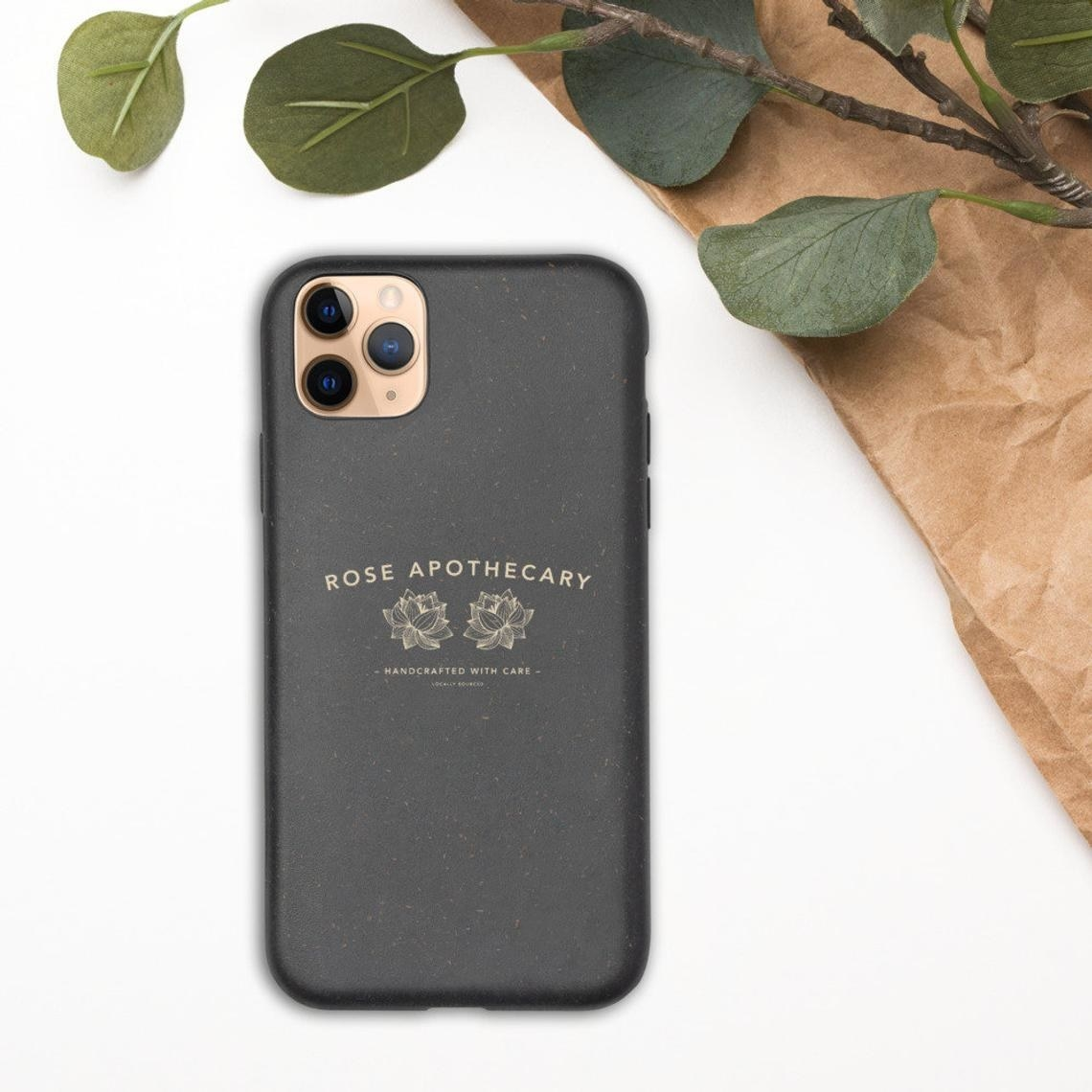 The case on a phone next to a plant and paper bag