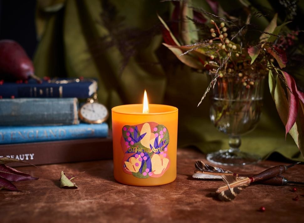 an orange candle with an abstract label on it