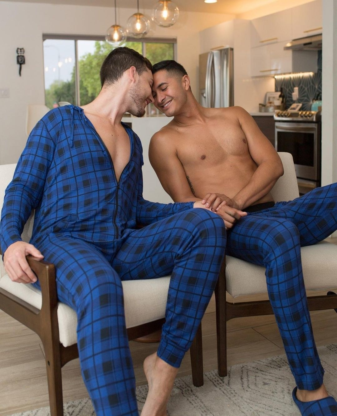 Two moodels, one in a blue plaid onesie, one in PJ pants in the same prinit