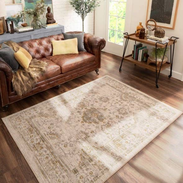 Living room with leather couch and beige distressed vintage rug