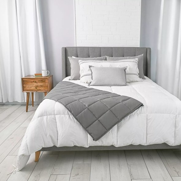 Grey weighted blanket on white bed