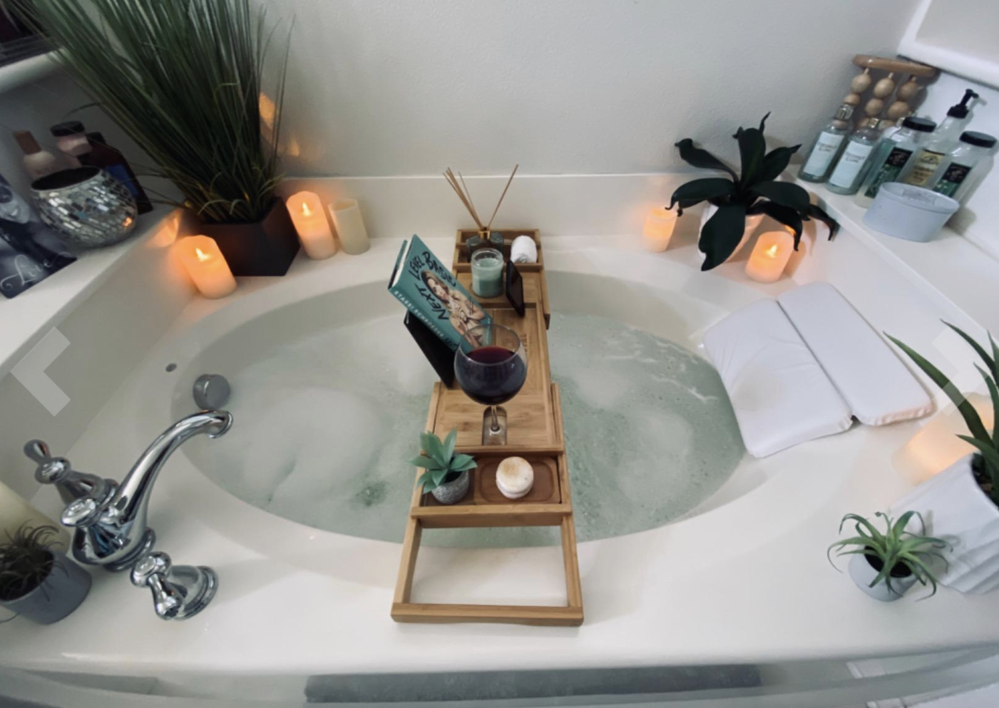 Reviewer image of the tray laid across a large jacuzzi with wine, plants, and a book set up on it