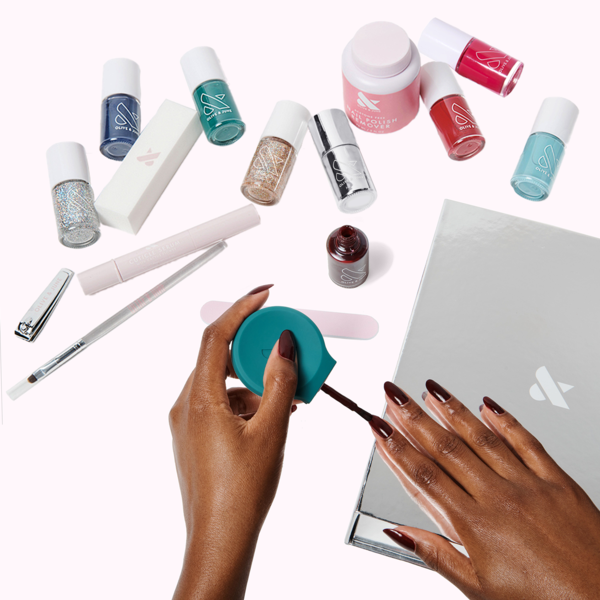 a model painting their nails with an array of nail polishes and polishing tools in the background