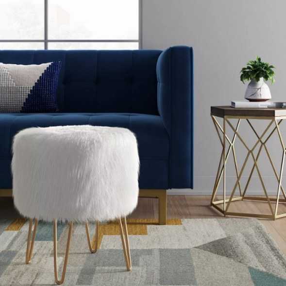 White fluffy ottoman with blue couch