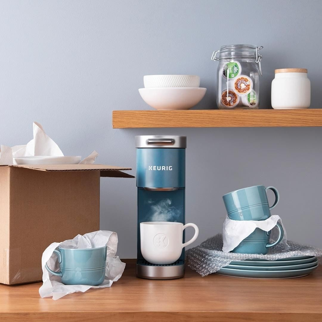 Mini Keurig surrounded by dinnerware