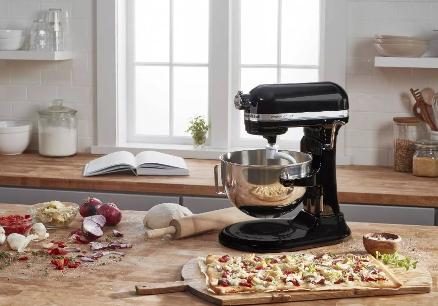 Black standing mixer with pizza near it