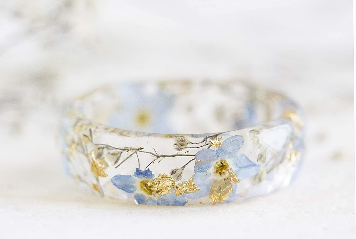 The clear faceted band with blue forget me nots and gold flake inside